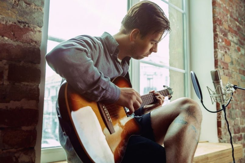 young-man-recording-music-playing-guitar-and-Q5K8HCJ